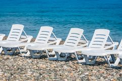 Four white plastic beach chairs on the beach Stock Photography