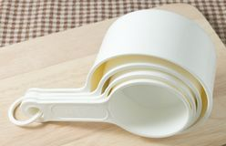 Four White Plastic Measuring Cups on Wooden Board Stock Photos