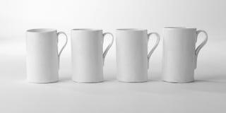 Four White Porcelain Mugs. High key studio shot of 4 fine white porcelain mugs with handles.  Handmade with white glossy glaze Stock Images