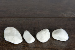 Four white rocks on brown wood Stock Photography
