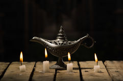 Four white wax candles sitting on wooden surface burning, Aladin style lamp placed behind, black background Royalty Free Stock Photo