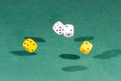 Four white and yellow dices falling on a green table royalty free stock photos