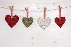 Four wicker hearts hanging on the rope. Valentines day background stock images