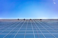 Four Window Washers Cleaning on the side of a skyscraper looking up stock photography