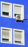 Four windows. Four white windows on the blue building and single airconditioner Stock Photography