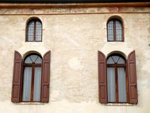 Four windows, two large, two small. Photo made in Noale in the province of Venice (Italy). Noale is a town of ancient origin, which is located about halfway stock photography