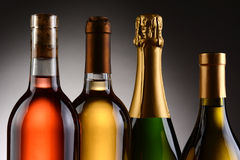 Four Wine Bottles Backlit. Closeup of four wine bottles backlit witha light to dark gray background. A Blush, Chardonnay, Sauvignon Blanc and Champagne bottles royalty free stock photos