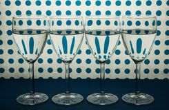 Four wine glasses standing in line and white background with blue spots. stock photo