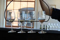 Four wine glasses in wrought iron holder, ready for tasting, Living Root Winery, Rochester, New York, 2017. Four beautifully etched wine glasses in wrought iron stock photos