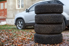 Four winter tyre wheels for changing are near car, copyspace. Nobody Royalty Free Stock Photography
