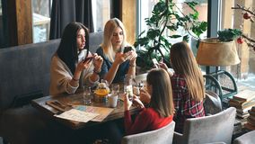 Four woman in cafe using app smartphone playing social network. Technology isolation stock video footage