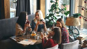 Four woman in cafe using app smartphone playing social network. Technology isolation stock video