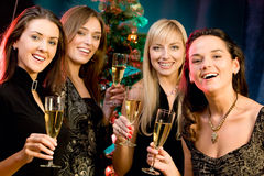 Four women. Portrait of four woman holding the glasses of champagne on the background of christmas-tree Royalty Free Stock Photo