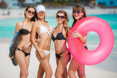 Four women in bikinis with lifeline near the ocean. Stock Image