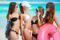 Four women in bikinis with lifeline near the ocean. Royalty Free Stock Images
