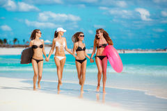 Four women in bikinis with lifeline near the ocean. Stock Photography