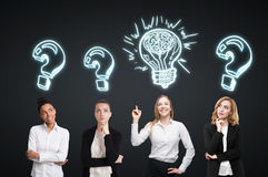 Four women brainstorm. Black wall. Sketches. Four women are standing near a black wall and looking for a problem solution. Light bulb sketch  drawn above one of Royalty Free Stock Photos