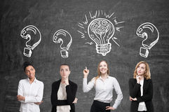 Four women brainstorm. Blackboard. Sketches. Four women are standing near a blackboard and looking for a problem solution. Light bulb sketch is drawn above one Stock Photos