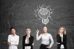 Four women brainstorm. Blackboardl. Light bulb. Four women are standing near a blackboard and looking for a problem solution. White light bulb sketch is above Royalty Free Stock Image