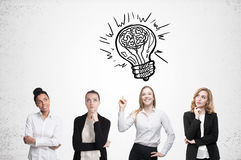 Four women brainstorm. Concrete wall. Light bulb. Four women are standing near a concrete wall and looking for a problem solution. Light bulb sketch is drawn Stock Photos