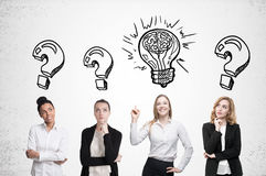 Four women brainstorm. Concrete wall. Sketches. Four women are standing near a concrete wall and looking for a problem solution. Light bulb sketch is drawn above Stock Photography