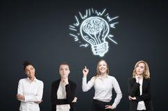 Four women brainstorm near black wall. Light bulb Stock Photo