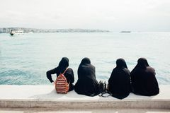 Four women in burka sit with their backs and look at the sea. With boats Royalty Free Stock Images
