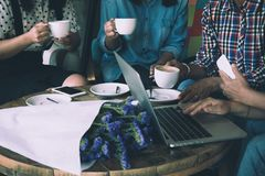 Four women do meeting by sharing information from notebook and drinking coffee in coffee shop with warm light flare tone. Photo with grain noise as film grain Royalty Free Stock Images