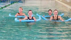 Four women doing aqua aerobics smiling at camera Royalty Free Stock Photography
