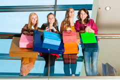 Four women friends shopping in a mall. Four female friends with shopping bags having fun while shopping in a mall, stores in the background royalty free stock photos
