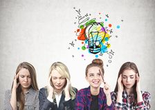 Four women with good idea. Four young women sitting near concrete wall and thinking hard. One of them has a good idea. Concept of brainstorming stock photography