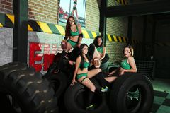 Four Women on Green Sport Bra and Shorts Near Tires Royalty Free Stock Photos