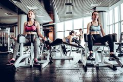 Four women in gym doing strength training on the simulator. The concept of sport. Front view royalty free stock photography