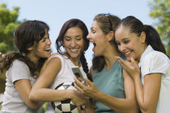 Four Women Laughing At Mobile Phone Display Stock Images