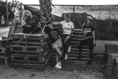 Four Women Leaning and Sitting on Pallets Royalty Free Stock Photo