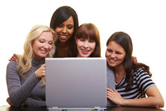Four women looking at a laptop Stock Image