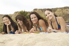 Four women lying down on Beach Royalty Free Stock Photography