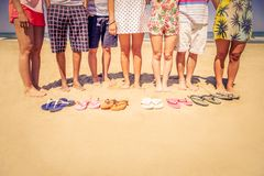 Four women outdoors. Group of friends on the beach with colored slippers on the sand - Tourists on vacation on a tropical beach during summertime Royalty Free Stock Photography