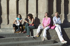 Four women relax in sunlight of old Barcelona in Barri Gotic area, the Gothic Quarter, Spain Royalty Free Stock Photo