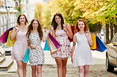 Four Women with Shopping Bags. Walking around. group Women Carrying Shopping Bags On City Street royalty free stock images