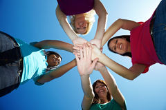Four women stacking their hands. Four young women stacking their hands on top of each other Stock Photography
