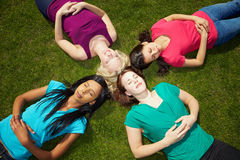 Four women sunbathing in a park Stock Photos