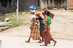 Four women walking on the road. In abidjan, there are women who walk each day to fetch dirty linenwashing what they have in hand is their work tools Stock Photos