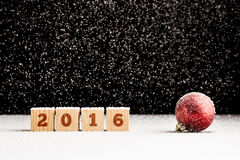 Four wooden cubes with 2016 sign on them laying on snowy surface Stock Photography