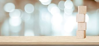Four wooden cubes on table over blur abstract bokeh light backgr Royalty Free Stock Image