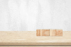 Four wooden cubes on table over white  wall background Royalty Free Stock Photography