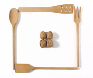 Four Wooden Kitchen Tools and Four Walnuts Stock Photos