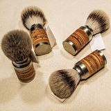 Four wooden shaving brushes on the canvas royalty free stock image