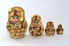 Four  wooden nested dolls on a white background close-up. Four decorated Russian wooden nested dolls on a white background close-up Royalty Free Stock Photos