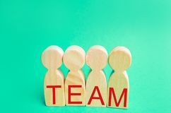 Four wooden people with the inscription `team`. group work. teamwork. achievement of goals, corporate spirit. cohesion in the team. Workers stock photo